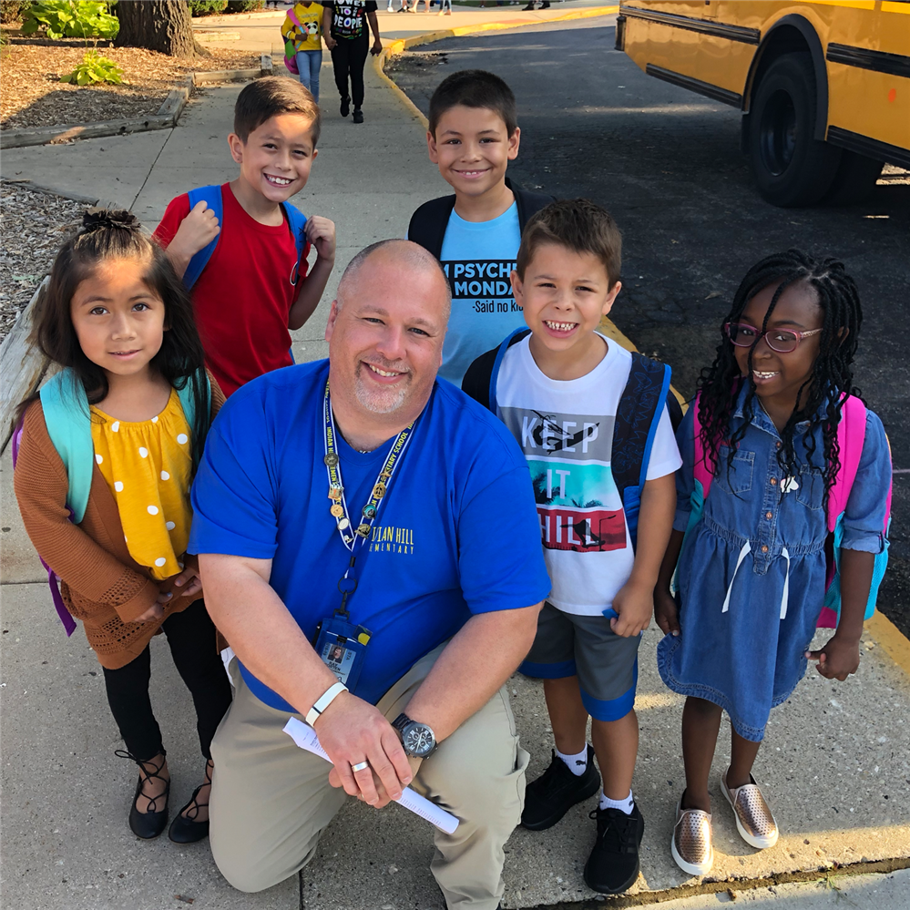 Principal Ray Porten with students out front of school for First Day of School